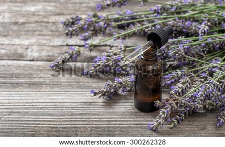 Herbal oil and lavender flowers bouquet on wooden background. Alternative home medicine. Selective focus - stock photo