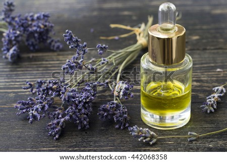 Herbal oil and lavender flowers on wooden background.Selective focus