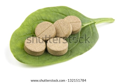 Herbal pills on green leaf isolated on white