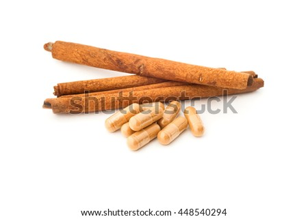 herbal powder in capsule and cinnamon on white background