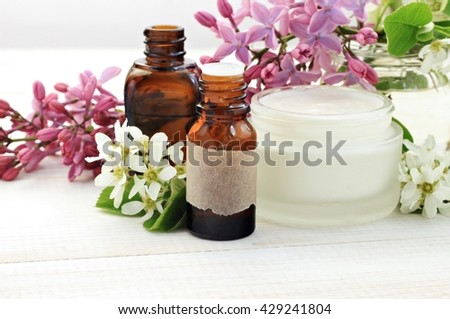 Herbal skincare beauty products. Essential oils, fresh facial cream. Lilac springtime flowers - stock photo