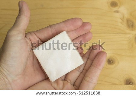 herbal soap in hand on wooden background
