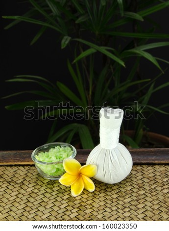 Herbal. Spa salt in a glass cup. And placed a frangipani spa set on a bamboo tree in the background is bright green. - stock photo