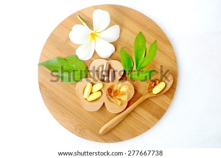 Herbal supplements and vitamins  on wooden tray, decorated with white flowers and green leafs background as white cotton cloth  - stock photo