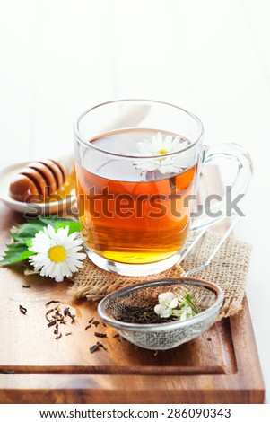 Herbal tea in a glass bowl with camomile flowers and honey on rustic wooden background, selective focus