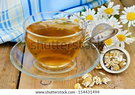 Herbal tea in a glass cup, a metal strainer with dried chamomile flowers, fresh flowers daisies, napkin against a wooden board - stock photo