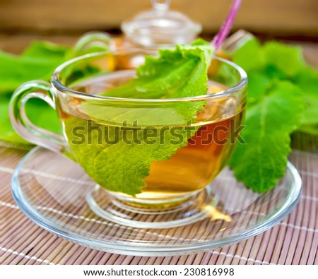 Herbal tea in a glass cup and saucer and teapot on background of sage leaves bamboo napkin and wooden planks - stock photo