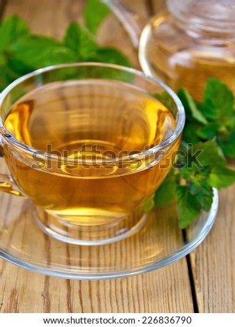 Herbal tea in a glass cup and teapot from mint, fresh mint leaves on a wooden boards background - stock photo