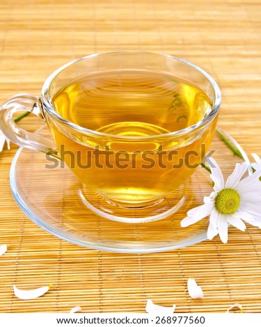 Herbal tea in a glass cup, camomile on a background of a bamboo napkin - stock photo