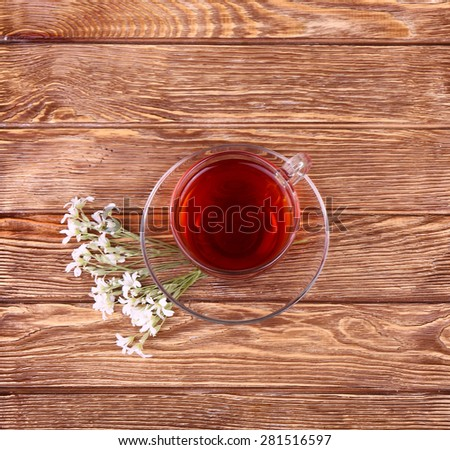 Herbal tea in a glass cup, fresh flowers on a background of wooden boards