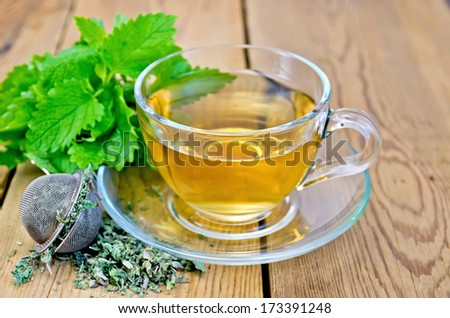 Herbal tea in a glass cup, metal sieve with dry mint, fresh leaves on the background of wooden boards