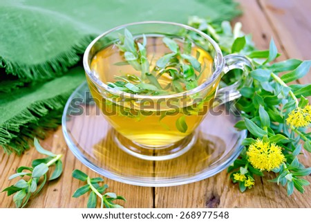 Herbal tea in a glass cup with flowers Rhodiola rosea, green cloth on a wooden board - stock photo