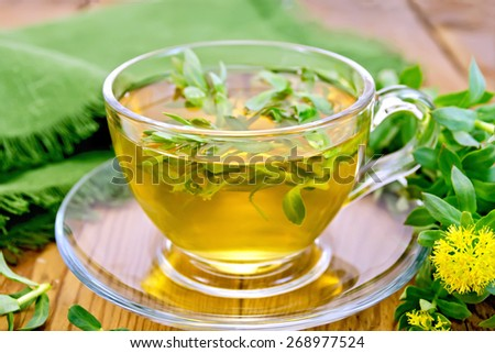 Herbal tea in a glass cup with flowers Rhodiola rosea, green cloth on a wooden boards background - stock photo