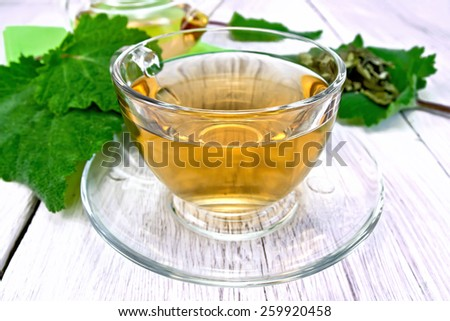 Herbal tea in a glass cup with saucer and teapot, sage leaves on the background light wooden boards - stock photo