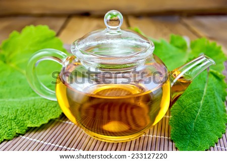 Herbal tea in a glass teapot, sage leaves on a bamboo napkin on a wooden boards background - stock photo
