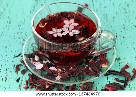 Herbal tea in glass cup, on color wooden background - stock photo