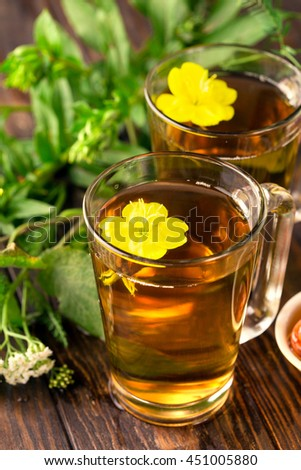 Herbal tea in glass cups with summer flowers and honey on rustic wooden background, selective focus