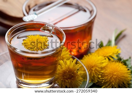 herbal tea infusion of fresh dandelion leaf, with yellow blossoms and honey - stock photo