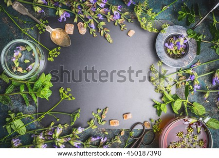 Herbal tea ingredients with various fresh herbs and flowers, cup of tea and tools on  black chalkboard background, top view, frame - stock photo