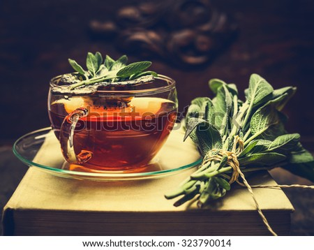 Herbal tea made from sage in glass cup standing on books, nearby lies a bundle of sage over dark wooden background. Retro toned.  - stock photo
