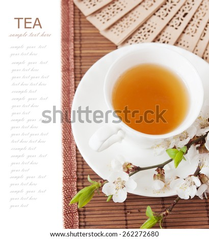 Herbal tea (tea breakfast with cup of tea and blossom flowers on bamboo mat isolated on white with sample text ) - stock photo