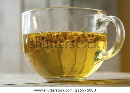 herbal tea with chamomile flowers, old wood table background