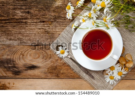 herbal tea with chamomile on old wooden table. Top view. - stock photo