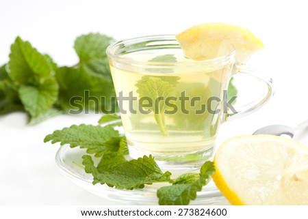 herbal tea with lemon beam in tea cup, sliced lemon, and fresh green melissa leaf on white background