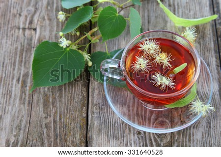 Herbal tea with linden on an old wooden table - stock photo