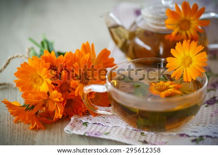 Herbal tea with marigold flowers on the table - stock photo