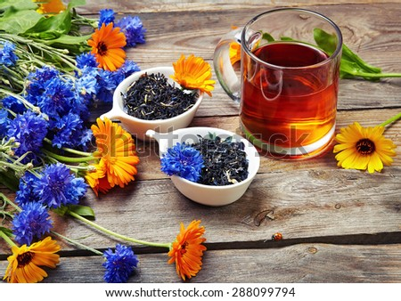 Herbal tea with wild flowers  on wooden background  - stock photo