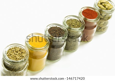 Herbs and spices in glass jars, isolated on white background - stock photo