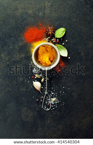 Herbs and spices selection (turmeric, paprika, basil, salt, papper) on dark rustic background - stock photo