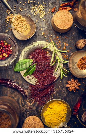 Herbs and spices selection with staghorn sumac powder on dark rustic wooden background, top view