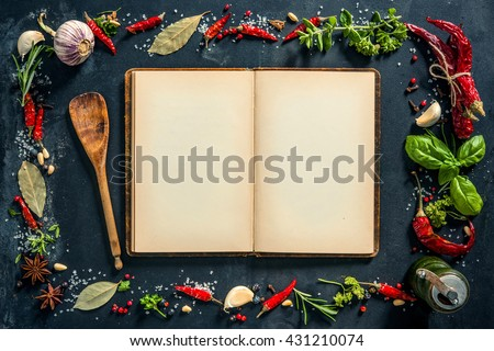 Herbs and spices with a recipe book over black stone background. Top view with copy space