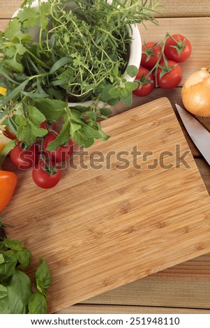 Herbs and vegetables with a blank chopping board. Space for copy.  - stock photo