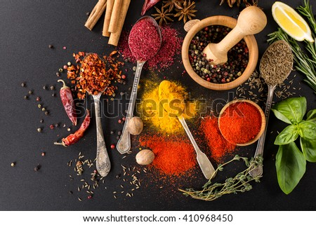 herbs condiments and spices on black background - stock photo