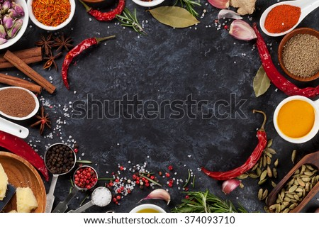 Herbs, condiments and spices on stone background. Top view with copy space - stock photo