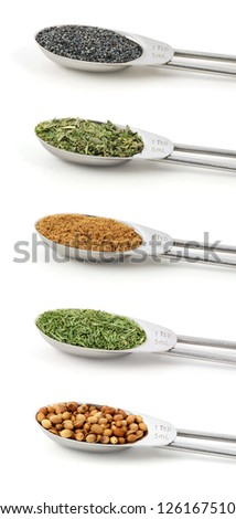 Herbs measured in metal teaspoons, isolated on a white background: Poppy seeds, dried mixed herbs, ground coriander / cilantro, dill tops, whole coriander / cilantro seeds. - stock photo