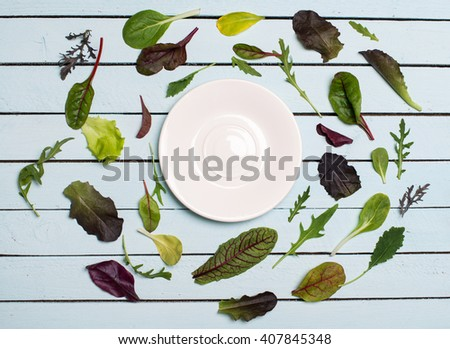 Herbs or salad mix leaves laid out around a white plate saucer with place for text, salad leaves frame on white wooden rustic background top view. - stock photo