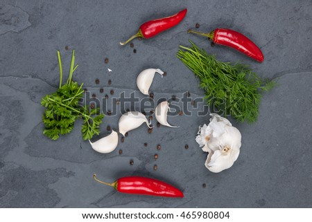 Herbs, pepper, and garlic on a grey cutting board, stock picture