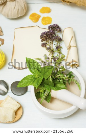 herbs, spices and massage pouches on white wooden table