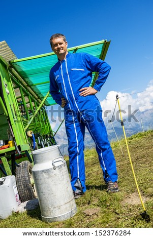 Herdsman standing in front of a machine milking cows - stock photo