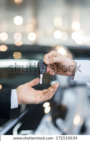 Here is your key! Close up of man giving key to the car owner while standing in front of a car - stock photo