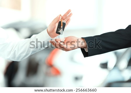 Here is your key. Closeup of man giving key to the car owner while standing in front of a car - stock photo