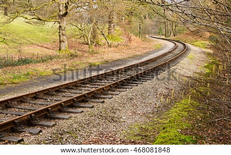 Heritage railway train tracks forming an S curve through a rural setting.