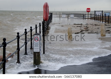 HERNE BAY, KENT, UK - DEC 6: The afternoon spring high tide, coupled with a storm surge just tops the sea defences at Hampton Pier, Herne Bay, Kent, UK on Dec 6, 2013. There appears to be no damage. - stock photo