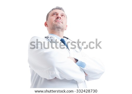 Hero shot in low angle of young doctor or medic standing confident with arms crossed isolated on white background - stock photo