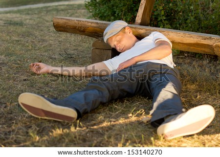 Heroin abuser passed out in the park after an overdose in summer - stock photo
