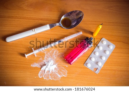 heroin drugs marijuana syringe and spoon and lighters and candle  - stock photo